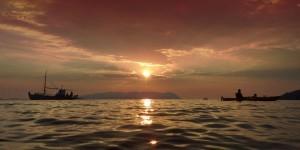 Fishing boat and sea kayak at sunset